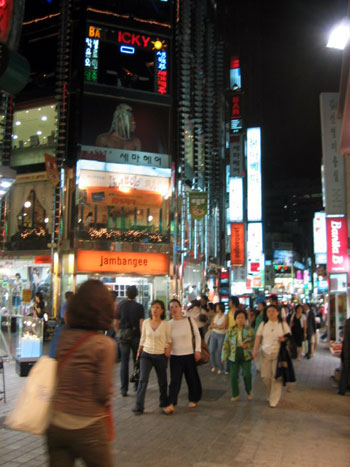 Nattebillede fra vores kvarter. Butikker og restauranter breder sig op i flere etager.
